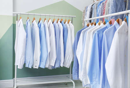 Racks with clean clothes on hangers after dry-cleaning indoors Banco de Imagens