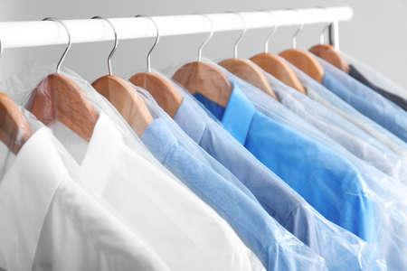 Perchero con ropa limpia en perchas después de la limpieza en seco Foto de archivo