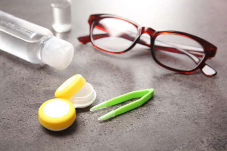 Glasses and contact lens accessories on grey background