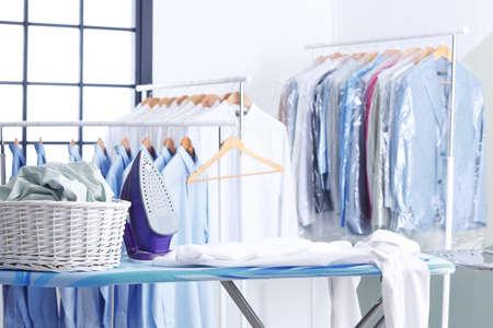 Cesto di vimini con vestiti sull'asse da stiro in lavanderia