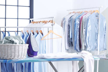 Weidenkorb mit Kleidung auf Bügelbrett bei der Reinigung