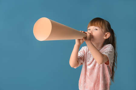 Cute little girl with paper megaphone on color background Stock Photo