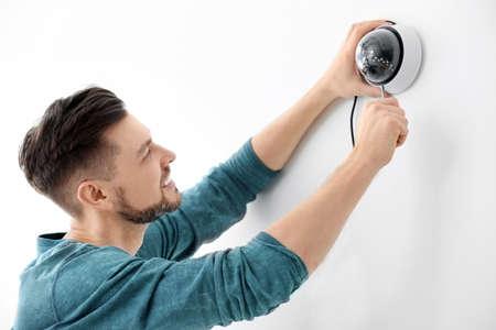 Technician installing CCTV camera on wall indoors Stock Photo - 106966170