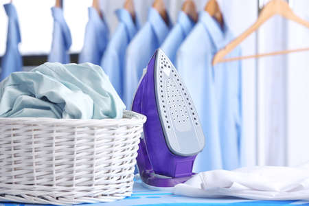 Wicker basket with clothes on ironing board at dry-cleaner's