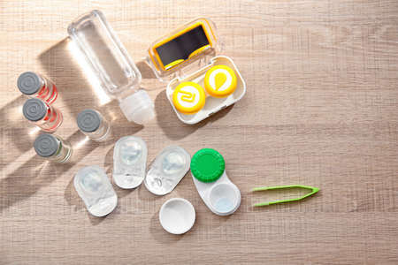 Contact lenses and accessories on wooden table Stock Photo