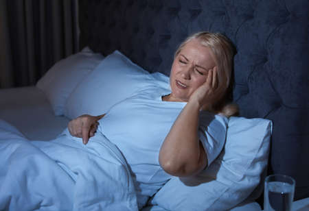 Mature woman suffering from headache in bed at night Banque d'images