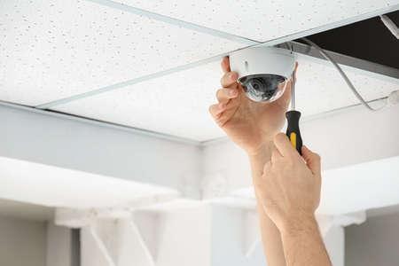 Technicus CCTV-camera installeren op plafond binnenshuis, close-up