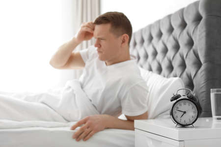 Alarm clock on nightstand of young man suffering from headache