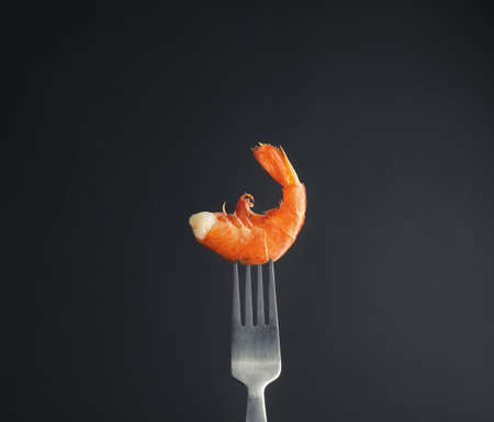 Fork with delicious shrimp on dark background