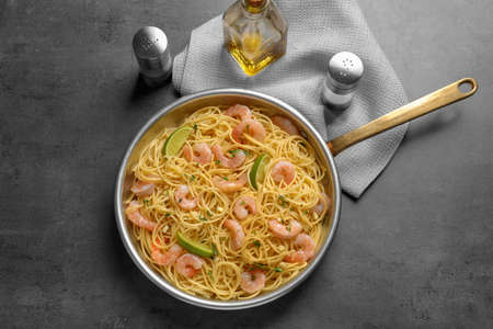 Frying pan with spaghetti and shrimps on grey background, top view