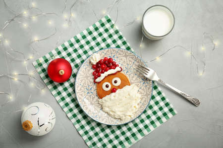 Flat lay composition with pancakes in form of Santa Claus on grey background. Christmas breakfast ideas for kids
