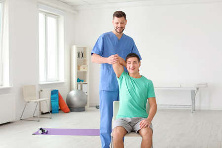 Physiotherapist working with male patient in clinic