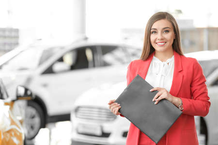 Young woman with clipboard in car salon
