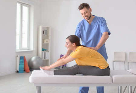 Physiotherapist working with female patient in clinic