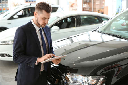 Salesman with tablet in salon. Buying new car