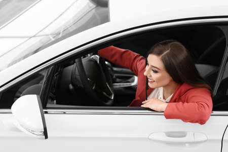 Young woman sitting in driver's seat of new car at salon Standard-Bild