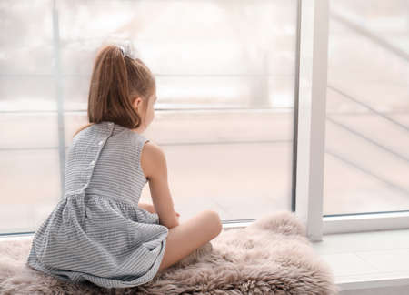 Lonely little girl sitting near window indoors. Child autism
