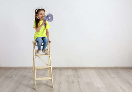 Cute little girl sitting with megaphone near white wall Banque d'images