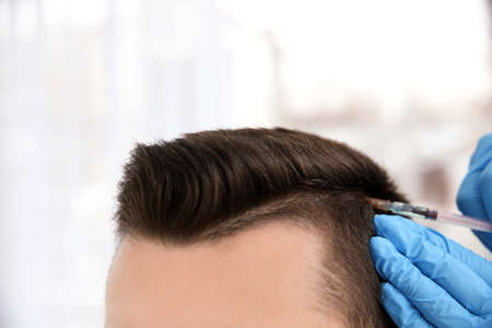 Young man with hair loss problem receiving injection on blurred background, closeup
