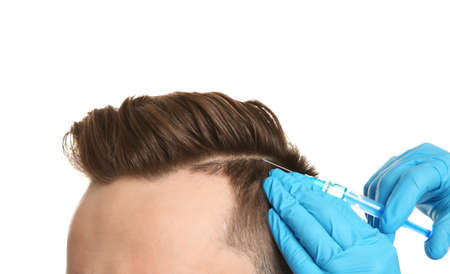 Young man with hair loss problem receiving injection on white background, closeup Stock Photo
