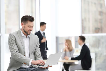 Portrait of handsome young businessman with laptop in office Reklamní fotografie