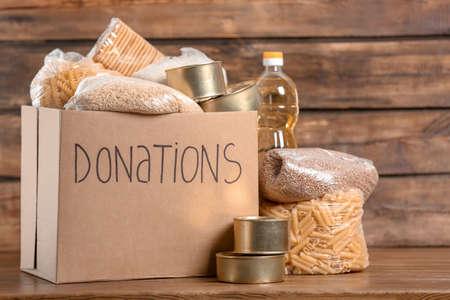 Boîte de don avec de la nourriture sur fond de bois