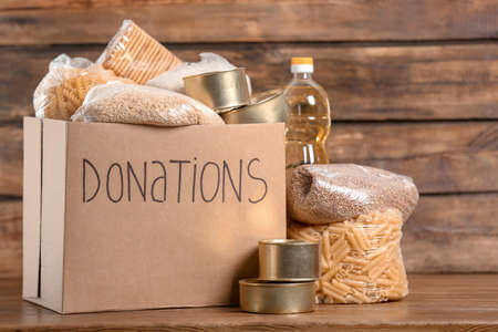 Donation box with food on wooden background
