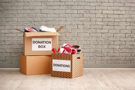 Donation boxes with clothes and shoes on floor against brick wall