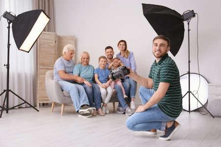 Professionele fotograaf die foto van familie op bank in studio neemt Stockfoto