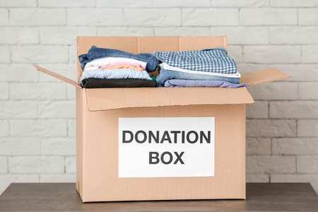 Donation box with clothes on table against brick wall Stock Photo