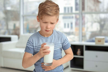 Little boy with dairy allergy holding glass of milk indoors