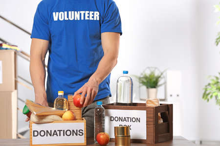 Male volunteer putting food products in donation boxes indoors