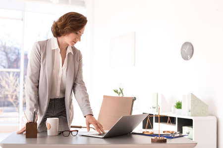 Female lawyer standing near table in office