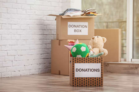 Donation boxes with toys and clothes on floor indoors