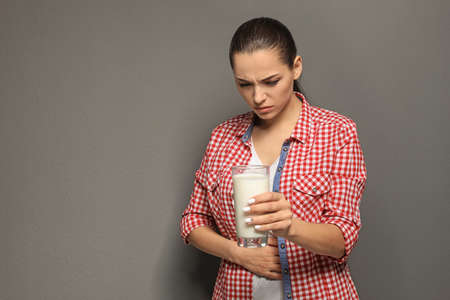 Mujer joven con alergia a los lácteos sosteniendo un vaso de leche sobre fondo gris Foto de archivo