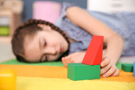 Little girl with autistic disorder playing at home, closeup of cubes Stock Photo