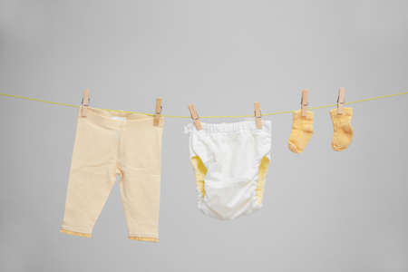 Baby clothes hanging on washing line against gray background Archivio Fotografico