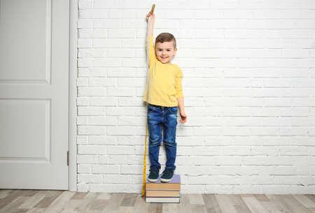 Little boy measuring his height near brick wall Foto de archivo - 105404102
