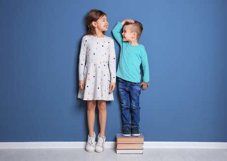 Niña y niño midiendo su altura cerca de la pared de color