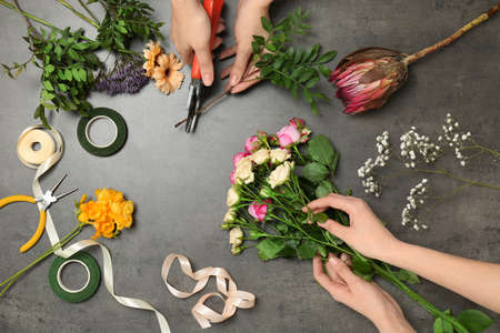 Female florists making beautiful bouquet at table, top view Imagens