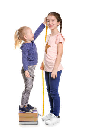 Little girls measuring their height on white background Archivio Fotografico