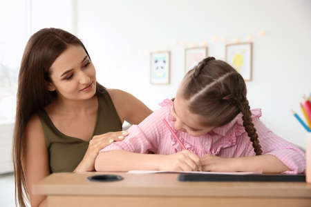 Young woman and little girl with autistic disorder drawing at home Stock Photo