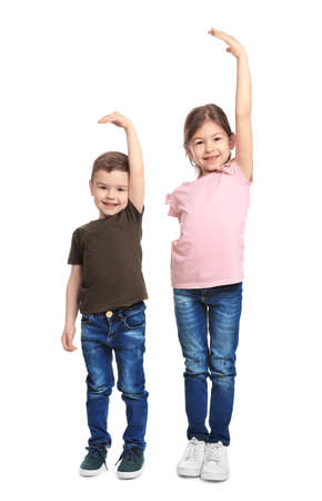 Little children measuring their height on white background Stock Photo