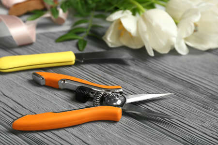 Florist workplace with pruning snips and knife on table
