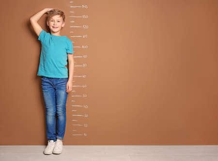 Ragazzino che misura la sua altezza vicino alla parete del colore