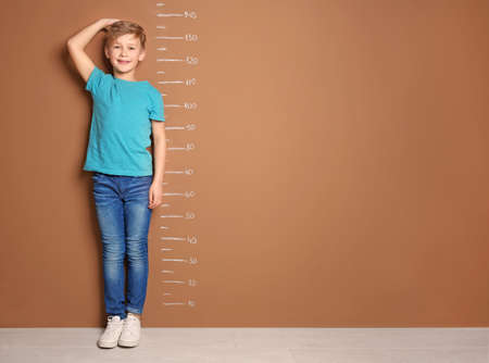 Weinig jongen die zijn lengte dichtbij kleurenmuur meet