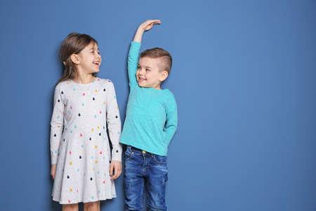 Klein meisje en jongen die hun lengte meten op gekleurde achtergrond Stockfoto