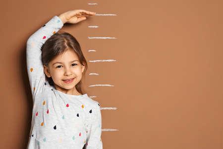 Niña midiendo su altura sobre fondo de color Foto de archivo