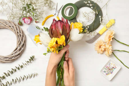 Female florist making beautiful bouquet at table, top view