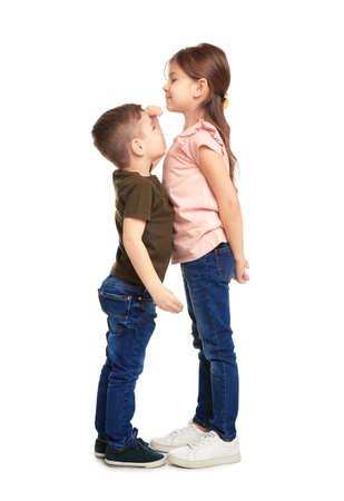 Los niños pequeños midiendo y comparando su altura sobre fondo blanco.